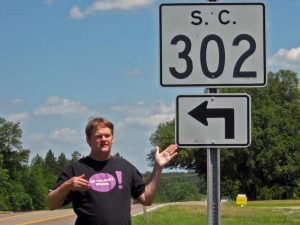 Man standing by a 302 redirect sign