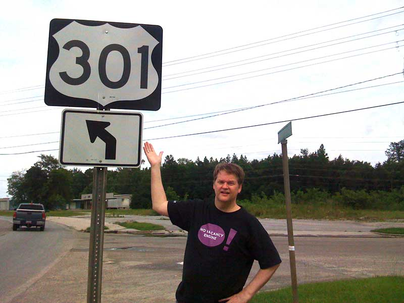 SEO Consultant and Founder of Leverable, Emory Rowland displaying a real-life 301 redirect (road sign)