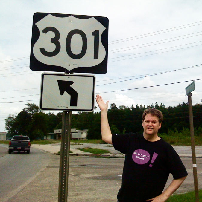 SEO Consultant, Emory Rowland displaying a real-life 301 redirect (road sign)